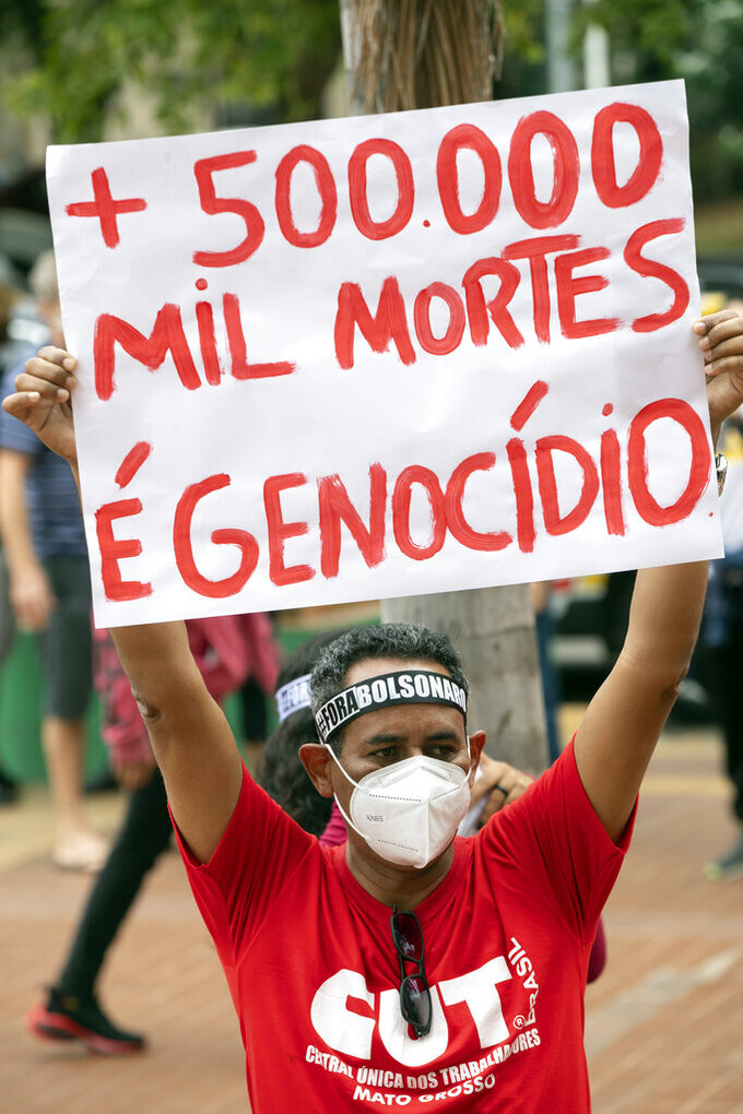 """A man, wearing a protective face mask, holds a sign with a message that reads in Portuguese; """"500,000 deaths is genocide"""", during a protest against Brazilian President Jair Bolsonaro and his handling of the pandemic and economic policies protesters say harm the interests of the poor and working class, in Cuiaba, Brazil, Saturday, June 19, 2021. Brazil is approaching an official COVID-19 death toll of 500,000 — second-highest in the world.(AP Photo/Andre Penner)"""