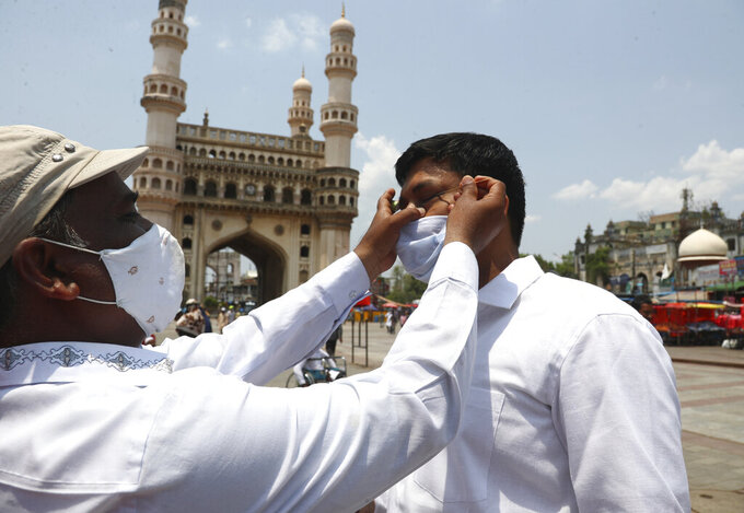 FILE- In this May 7, 2021, file photo, an Indian Muslim wearing face mask as a precaution against coronavirus gets his eyes lined with a black ointment called Surma before offering last Friday prayers of Ramadan at Mecca Mosque in Hyderabad, India. Misinformation about the coronavirus is surging in India as the death toll from COVID-19 rises. Fueled by anguish, distrust and political polarization, the claims are further compounding India's crisis. (AP Photo /Mahesh Kumar A, File)