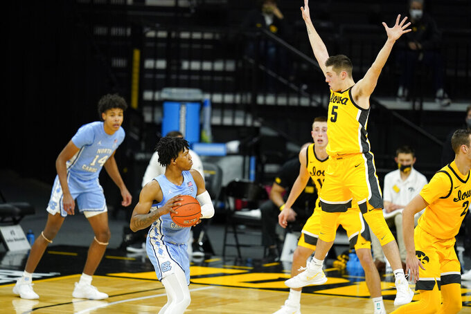 North Carolina guard Caleb Love looks to pass around Iowa guard CJ Fredrick (5) during the first half of an NCAA college basketball game, Tuesday, Dec. 8, 2020, in Iowa City, Iowa. (AP Photo/Charlie Neibergall)