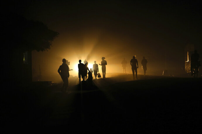 People walk home in the dark due to power shortages in Harare, on Monday Sept. 30, 2019. Zimbabwean President Emmerson Mnangagwa is set to present a State of the Nation address Tuesday, at a time the southern African nation is reeling from its worst economic crisis in more than a decade. Zimbabweans are enduring shortages of everything from medicines, fuel, cash and water- bringing a weariness and disgust that has often flared into streets protests. (AP Photo/Tsvangirayi Mukwazhi)