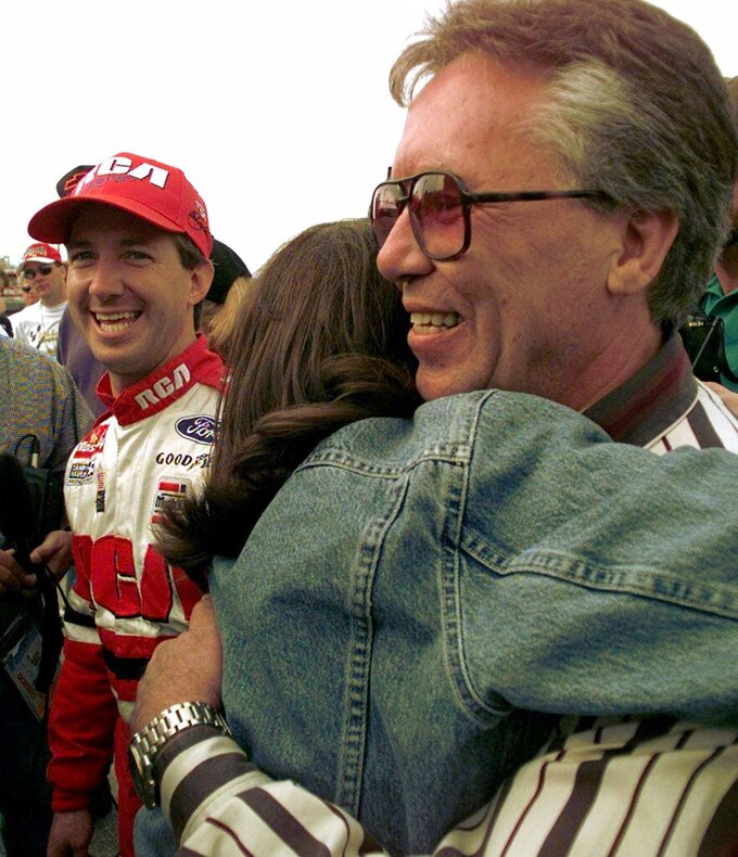 FILE - In this April 25, 1997, file photo, John Andretti, left, grins as his wife Nancy hugs his father Aldo after the younger Andretti won the pole for the Winston 500 at Talladega Superspeedway in Talladega, Ala. Mario Andretti feels the same pain as so many others these days. His wife died two years ago, long before the pandemic. And his beloved nephew John lost a brutal battle with colon cancer. But then COVID-19 claimed his twin brother Aldo and one of the greatest racers of all time is not immune from the loneliness and depression sweeping the world. (AP Photo/Dave Martin, File)