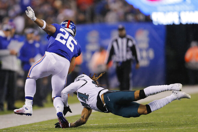 New York Giants running back Saquon Barkley (26) runs with the ball past Philadelphia Eagles wide receiver Robert Davis (14) in the first half of an NFL football game, Sunday, Dec. 29, 2019, in East Rutherford, N.J. (AP Photo/Adam Hunger)