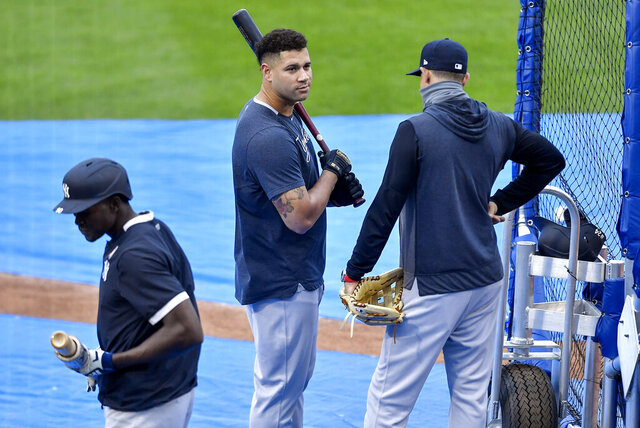 New York Yankees catcher Gary Sánchez, center, talks with manager Aaron Boone, right, during batting practice before a baseball game against the Toronto Blue Jays in Buffalo, N.Y., Monday, Sept. 7, 2020. (AP Photo/Adrian Kraus)