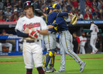 Milwaukee Brewers relief pitcher Josh Hader right, hugs catcher Omar Narvaez as Cleveland Indians' Myles Straw walks off the field after the final out of a baseball game in Cleveland, Saturday, Sept. 11, 2021. Hader combined with starting pitcher Corbin Burnes for a no-hitter. (AP Photo/Phil Long)
