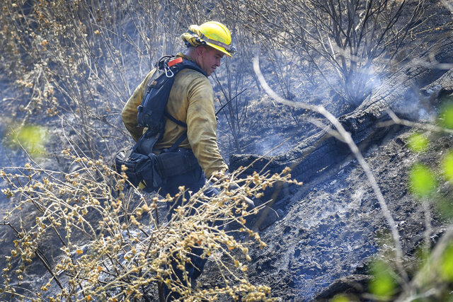 A firefighter works to knock down hot spots on a hillside along Mineral Spring Road west of Coalinga, Calif., while fighting the Mineral Fire on Thursday, July 16, 2020. Firefighters aided by helicopters and air tankers battled a 26 square mile (66.7 square kilometers) wildfire in a rural area of Central California that is 20% contained, a fire command statement said. (Craig Kohlruss/The Fresno Bee via AP)