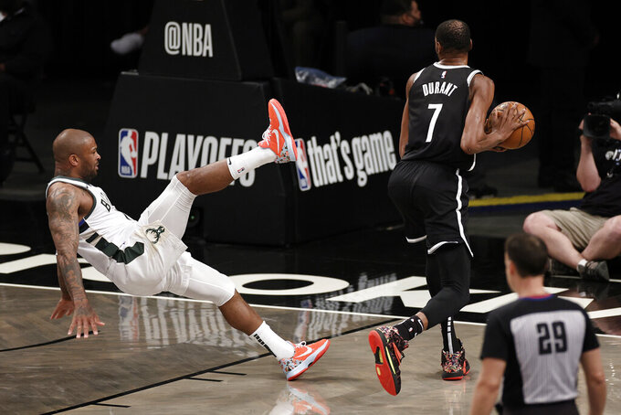 Brooklyn Nets forward Kevin Durant (7) shakes off Milwaukee Bucks forward P.J. Tucker during the first half of Game 1 of an NBA basketball second-round playoff series Saturday, June 5, 2021, in New York. (AP Photo/Adam Hunger)