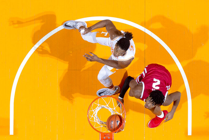 Wisconsin forward Aleem Ford (2) and Tennessee guard/forward Yves Pons (35) eye the ball as it falls into the net during an NCAA college basketball game, Saturday, Dec. 28, 2019 in Knoxville, Tenn. on Saturday, Dec. 28, 2019. (Calvin Mattheis/Knoxville News Sentinel via AP)