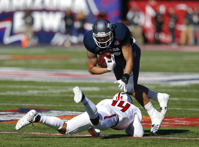 Nevada tight end Trae Carter-Wells breaks the tackle on Arkansas State defensive back Antonio Fletcher (14) in the first half of the Arizona Bowl NCAA college football game Saturday, Dec. 29, 2018, in Tucson, Ariz. (AP Photo/Rick Scuteri)