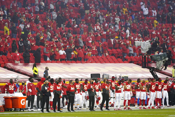 Kansas City Chiefs players and fans stand during the national anthem before an NFL football game against the Houston Texans Thursday, Sept. 10, 2020, in Kansas City, Mo. (AP Photo/Jeff Roberson)