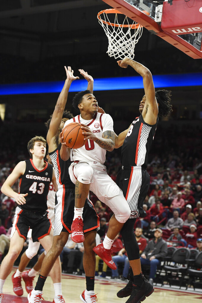 Arkansas guard Desi Sills (0) tries to get past Georgia defenders Nicolas Claxton (33), right, and Christian Harrison (11), left, as he drives to the hoop during the first half of an NCAA college basketball game, Tuesday, Jan.29, 2019 in Fayetteville, Ark. (AP Photo/Michael Woods)