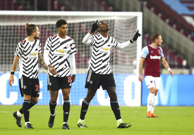 Manchester United's Paul Pogba celebrates after scoring his side's opening goal during the English Premier League soccer match between West Ham United and Manchester United at the London stadium in London, England, Saturday, Dec. 5, 2020. (Julian Finney/Pool Via AP)