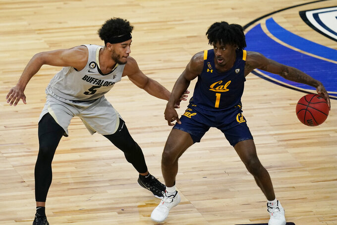 California's Joel Brown (1) drives into Colorado's D'Shawn Schwartz (5) during the first half of an NCAA college basketball game in the quarterfinal round of the Pac-12 men's tournament Thursday, March 11, 2021, in Las Vegas. (AP Photo/John Locher)