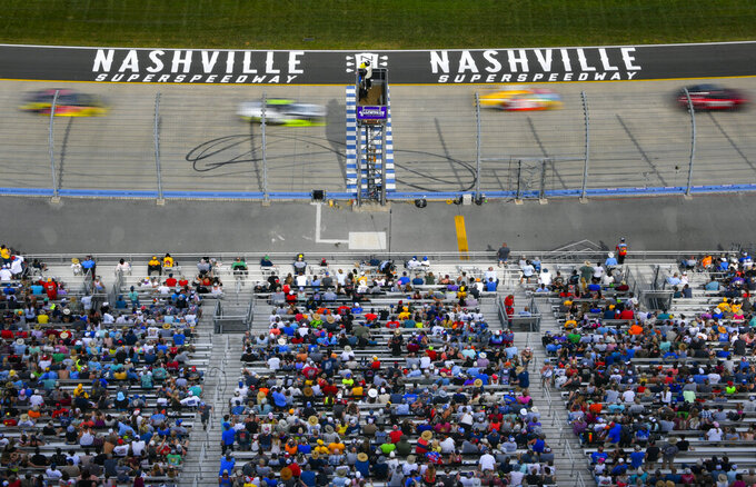 Fans watch a NASCAR Xfinity Series auto race underway Saturday, June 19, 2021, at Nashville Superspeedway in Lebanon, Tenn. (AP Photo/John Amis)