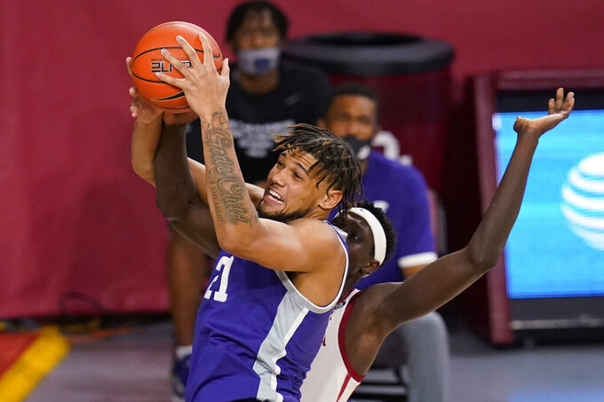 Kansas State forward Davion Bradford (21) grabs a rebound in front of Oklahoma forward Kur Kuath, right, during the first half of an NCAA college basketball game Tuesday, Jan. 19, 2021, in Norman, Okla. (AP Photo/Sue Ogrocki)