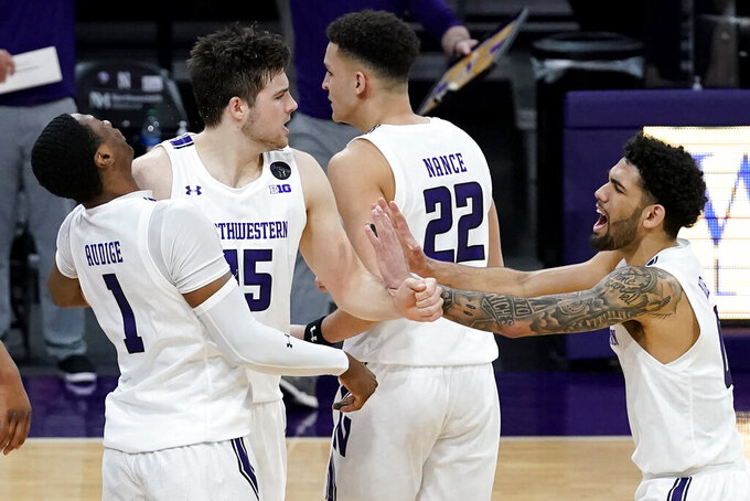 Northwestern center Ryan Young, second from left, celebrates with guard Chase Audige, left, and guard Boo Buie after scoring a basket against Nebraska during the second half of an NCAA college basketball game in Evanston, Ill., Sunday, March 7, 2021. (AP Photo/Nam Y. Huh)