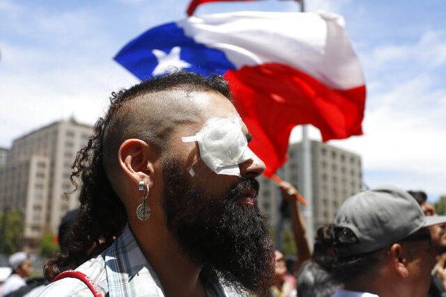 Marcelo Herrera, a demonstrator who claims he lost an eye after being shot with a shotgun by the police during the ongoing anti-government demonstrations, joins a protest in front of Palacio de La Moneda, in Santiago, Chile, Friday, Dec. 13, 2019. The United Nations released on Friday a report which stated that there have been serious violations of human rights during the repression of recent protests in Chile. (AP Photo/Luis Hidalgo)