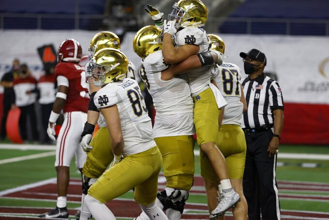 Notre Dame running back Kyren Williams, being lifted, celebrates with tight end George Takacn (85) and tight end Michael Mayer (87) and others after scoring a touchdown on a run in the first half of the Rose Bowl NCAA college football game against Alabama in Arlington, Texas, Friday, Jan. 1, 2021. (AP Photo/Ron Jenkins)