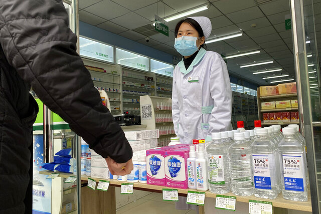 A pharmacy worker attends to visitors at the store entrance in Beijing, China on Thursday, Feb. 20, 2020. A viral outbreak that began in China has infected more than 75,000 people globally. The World Health Organization has named the illness COVID-19, referring to its origin late last year and the coronavirus that causes it.  (AP Photo/Ng Han Guan)