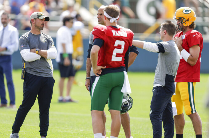 Green Bay Packers head coach Matt LaFleur and quarterback Aaron Rodgers (12) talk with New York Jets head coach Robert Saleh, quarterback Zach Wilson (2) and offensive coordinator Mike LaFleur during a joint NFL football training camp practice Wednesday, Aug. 18, 2021, in Green Bay, Wis. (AP Photo/Matt Ludtke)