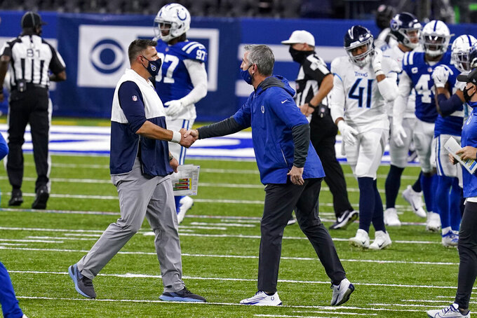 Tennessee Titans head coach Mike Vrabel, left, meets with Indianapolis Colts head coach Frank Reich following an NFL football game in Indianapolis, Sunday, Nov. 29, 2020. The Titans defeated the Colts 45-26. (AP Photo/Darron Cummings)