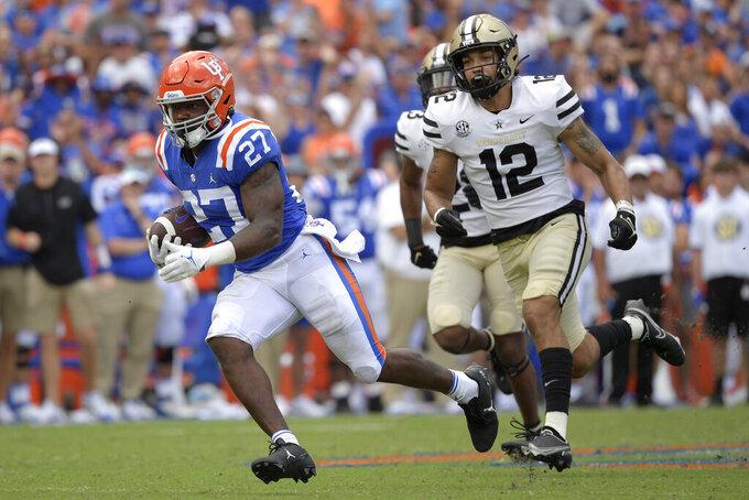 Florida running back Dameon Pierce (27) runs after catching a pass in front of Vanderbilt cornerback Jaylen Mahoney (23) and linebacker Brayden DeVault-Smith (12) for a 61-yard touchdown during the second half of an NCAA college football game, Saturday, Oct. 9, 2021, in Gainesville, Fla. (AP Photo/Phelan M. Ebenhack)