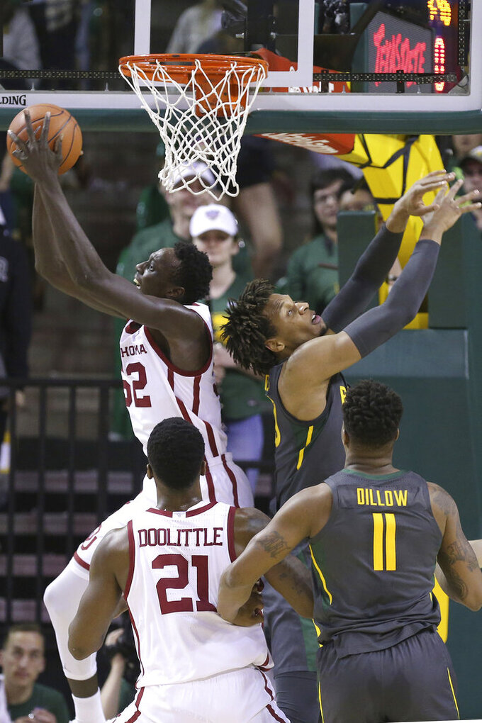 Oklahoma forward Kur Kuath (52) grabs the rebound against Baylor forward Freddie Gillespie (33) in the first half of an NCAA college basketball game Monday, Jan. 20, 2020, in Waco, Texas. (AP Photo/ Jerry Larson)
