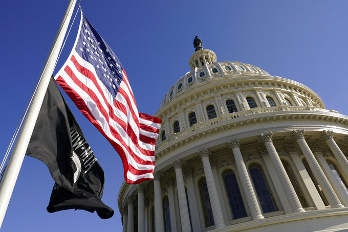 Flags fly on the U.S. Capitol in Washington, Tuesday, Jan. 19, 2021, ahead of the 59th Presidential Inauguration on Wednesday. (AP Photo/Susan Walsh, Pool)