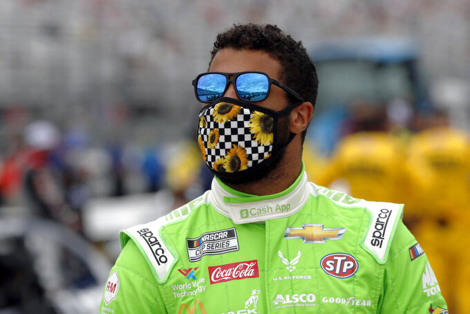 "FILE - Driver Bubba Wallace waits for the start of a NASCAR Cup Series auto race at New Hampshire Motor Speedway in Loudon, N.H., in this Sunday, Aug. 2, 2020, file photo. 23XI Racing announced a full slate of sponsorship Monday, Dec. 14, 2020, to back the new NASCAR team owned by Michael Jordan and Denny Hamlin.  DoorDash, McDonald's, Columbia Sportswear, Dr Pepper and Root Insurance were all named ""founding partners"" for the No. 23 Toyota Camry that Bubba Wallace will drive next season.(AP Photo/Charles Krupa, File)"