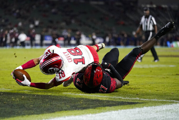 Utah wide receiver Britain Covey (18) reaches over the goal line for a touchdown while being tackled by San Diego State safety Cedarious Barfield (27) during the second half of an NCAA college football game Saturday, Sept. 18, 2021, in Carson, Calif. (AP Photo/Ashley Landis)