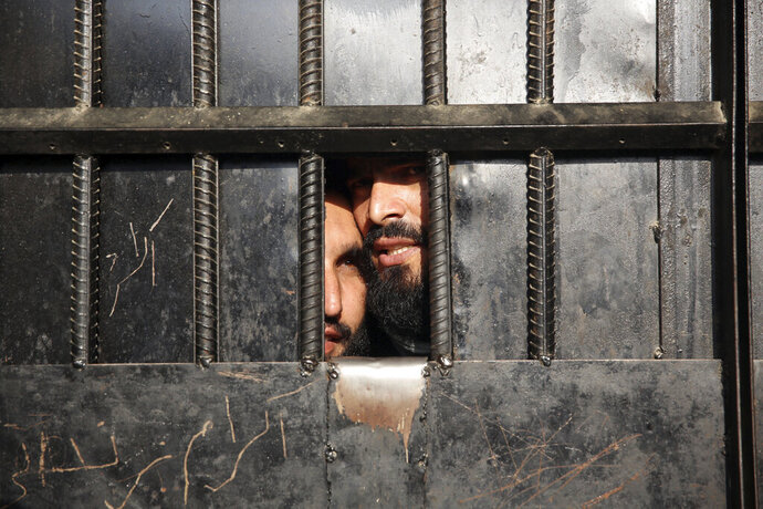 In this Monday, Aug. 3, 2020 file photo, Taliban prisoners watch through the door inside the prison after an attack in the city of Jalalabad, east of Kabul, Afghanistan. Afghanistan has been at war for more than 40 years, first against the invading Soviet army that killed more than 1 million people, then feuding mujahedin groups in a bitter civil war followed by the repressive Taliban rule and finally the latest war that began after the 2001 U.S.-led coalition invasion that toppled the Taliban government. (AP Photo/Rahmat Gul, File)