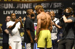Floyd Mayweather, left, and Logan Paul pose for photographers during a weigh-in Saturday, June 5, 2021, in Hollywood, Fla. Paul is scheduled to fight Mayweather in an exhibition boxing match at Hard Rock Stadium in Miami Gardens, Fla., Sunday. (AP Photo/Jim Rassol)