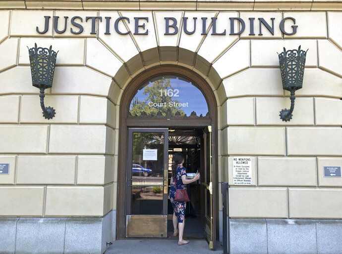 A woman enters the Oregon Department of Justice building in Salem, Ore., Thursday, May 28, 2020, the same day that the state supreme court and the appeals court began reversing convictions by nonunanimous juries. The U.S. Supreme Court in April ruled that nonunanimous jury convictions are unconstitutional. (AP Photo/Andrew Selsky)
