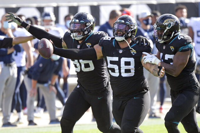 Jacksonville Jaguars defensive tackle Doug Costin (58) celebrates with defensive end Adam Gotsis, left, and linebacker Joe Giles-Harris (43) after recovering a Tennessee Titans during the first half of an NFL football game, Sunday, Dec. 13, 2020, in Jacksonville, Fla. (AP Photo/Phelan M. Ebenhack)
