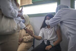 A girl holds her mother's hand while receiving her COVID-19 vaccine as Morocco launches a campaign to vaccinate 12-17 year olds before the start of the school year, in Rabat, Morocco, Tuesday, Aug. 31, 2021. (AP Photo/Mosa'ab Elshamy)