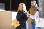 Jenny Cudd, front, a flower shop owner and former Midland mayoral candidate, and Eliel Rosa leave the federal courthouse in Midland, Texas, Wednesday, Jan. 13, 2021. The FBI arrested Cudd and Rosa on Wednesday in connection with the Jan. 6 insurrection at the U.S Capitol.  (Jacob Ford/Odessa American via AP)