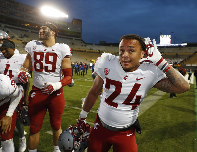Washington State running back Keith Harrington gestures to the crowd as his teammates assemble to sing the school song after an NCAA college football game against Colorado Saturday, Nov. 10, 2018, in Boulder, Colo. Washington State won 31-7. (AP Photo/David Zalubowski)