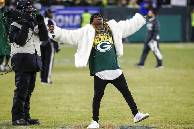 Rapper Lil Wayne sings during a break during the second half of an NFL divisional playoff football game between the Green Bay Packers and the Seattle Seahawks Sunday, Jan. 12, 2020, in Green Bay, Wis. (AP Photo/Matt Ludtke)