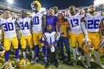 LSU coach Ed Orgeron; his wife, Kelly; and players celebrate the team's 56-20 victory over Arkansas in an NCAA college football game in Baton Rouge, La., Saturday, Nov. 23, 2019. (AP Photo/Matthew Hinton)