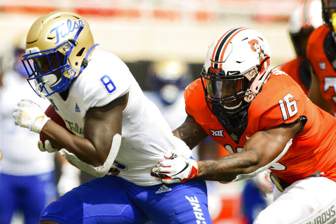 Tulsa running back Deneric Prince (8) struggles to escape Oklahoma State cornerback Rodarius Williams (16) in the second half of an NCAA college football game Saturday, Sept. 19, 2020, in Stillwater, Okla. (AP Photo/Brody Schmidt)
