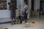 Austrian tourists with a dog arrive at the Acropolian Spirit Hotel in central Athens. on Monday June 1, 2020. Lockdown restrictions were lifted on non-seasonal hotels Monday as the country prepares to start its tourism season on June 15. (AP Photo/Petros Giannakouris)