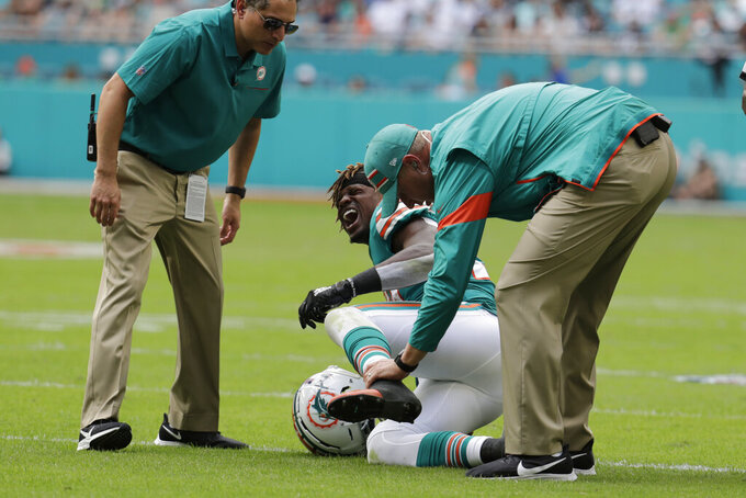 In this Sunday, Dec. 1, 2019, photo, Miami Dolphins running back Kalen Ballage (27) grimaces after an injury during the first half at an NFL football game against the Philadelphia Eagles, in Miami Gardens, Fla. Ballage's historically unproductive season ended Tuesday, Dec. 3 when he was placed on injured reserve by the Dolphins. (AP Photo/Lynne Sladky)