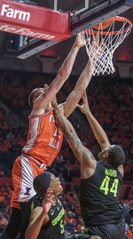 Illinois forward Giorgi Bezhanishvili (15) puts in a shot over Michigan State guard Cassius Winston (5) and forward Nick Ward (44) during the first half of an NCAA college basketball game in Champaign, Ill., Tuesday, Feb. 5, 2019. (AP Photo/Rick Danzl)