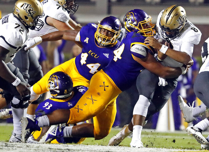 Central Florida's Darriel Mack Jr. (8) is tackled by East Carolina's Alex Turner (94) with Kendall Futrell (44) looking on during the first half of an NCAA college football game in Greenville, N.C., Saturday, Oct. 20, 2018. (AP Photo/Karl B DeBlaker)