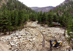 In this Friday, Aug. 6, 2021 photo, an excavator works along Black Hollow Road in Poudre Canyon, which was inundated with silt and rocks after flooding from the Cameron Peak Fire burn scar, near Red Feather Lakes, Colo. (Kevin J. Beaty/Colorado Public Radio via AP)