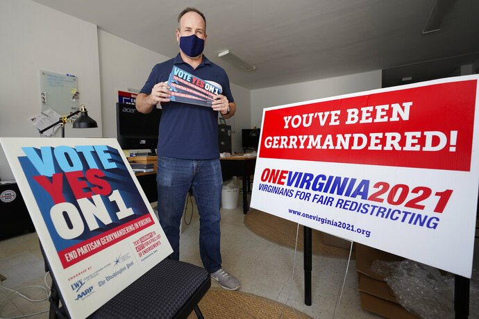 Redistricting reform advocate Brian Cannon poses with some of his yard signs and bumper stickers in his office, Tuesday Oct. 6, 2020, in Richmond, Va.  An effort to end centuries of partisan gerrymandering in Virginia is up for consideration by the state's voters. A referendum on the November ballot asks whether to amend the state Constitution to create a bipartisan panel that would take on the once-every-10-year task of redrawing the legislative boundaries for General Assembly and congressional districts  (AP Photo/Steve Helber)