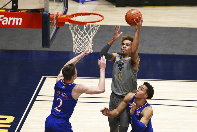 West Virginia forward Emmitt Matthews Jr. (11) shoots while defended by Kansas guard Christian Braun (2) and forward Jalen Wilson (10) during the first half of an NCAA college basketball game Saturday, Feb. 6, 2021, in Morgantown, W.Va. (AP Photo/Kathleen Batten)