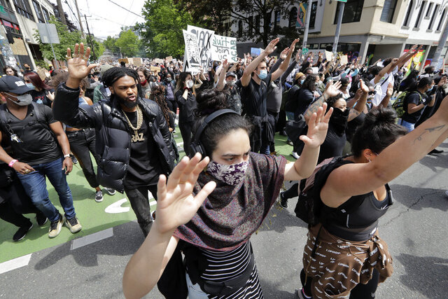 Demonstrators leave a rally and head toward Seattle City Hall Wednesday, June 3, 2020, in Seattle, following protests over the death of George Floyd, a black man who died in police custody in Minneapolis. (AP Photo/Elaine Thompson)