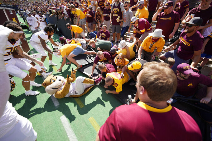 Minnesota fans collapse the fence around the field and trap masoct Goldy the Golden Gopher after an NCAA college football game against Colorado Saturday, Sept. 18, 2021, in Boulder, Colo. Minnesota won 30-0. (AP Photo/David Zalubowski)