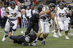 ETSU quarterback Trey Mitchell (5) is sacked by Vanderbilt linebacker Kenny Hebert (21) and defensive lineman Dayo Odeyingbo (10) in the first half of an NCAA college football game Saturday, Nov. 23, 2019, in Nashville, Tenn. (AP Photo/Mark Humphrey)