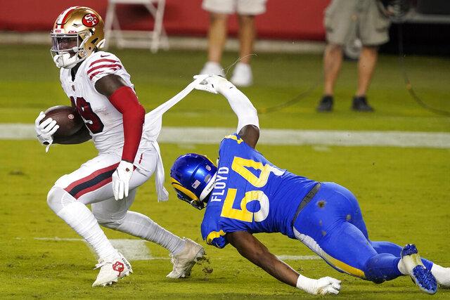Los Angeles Rams outside linebacker Leonard Floyd (54) tackles San Francisco 49ers wide receiver Deebo Samuel during the second half of an NFL football game in Santa Clara, Calif., Sunday, Oct. 18, 2020. (AP Photo/Tony Avelar)